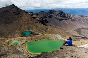 Tramper sitting looking over Green lake on Tongariro Alpine Crossing