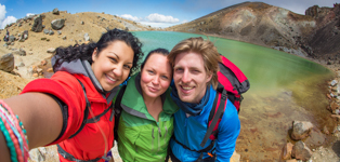 Three girl trampers doing selfie photograph at green lake Tongariro Crossing