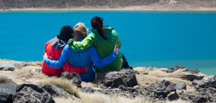 Three trampers sitting at Blue Lake on the Tongariro Alpine Crossing