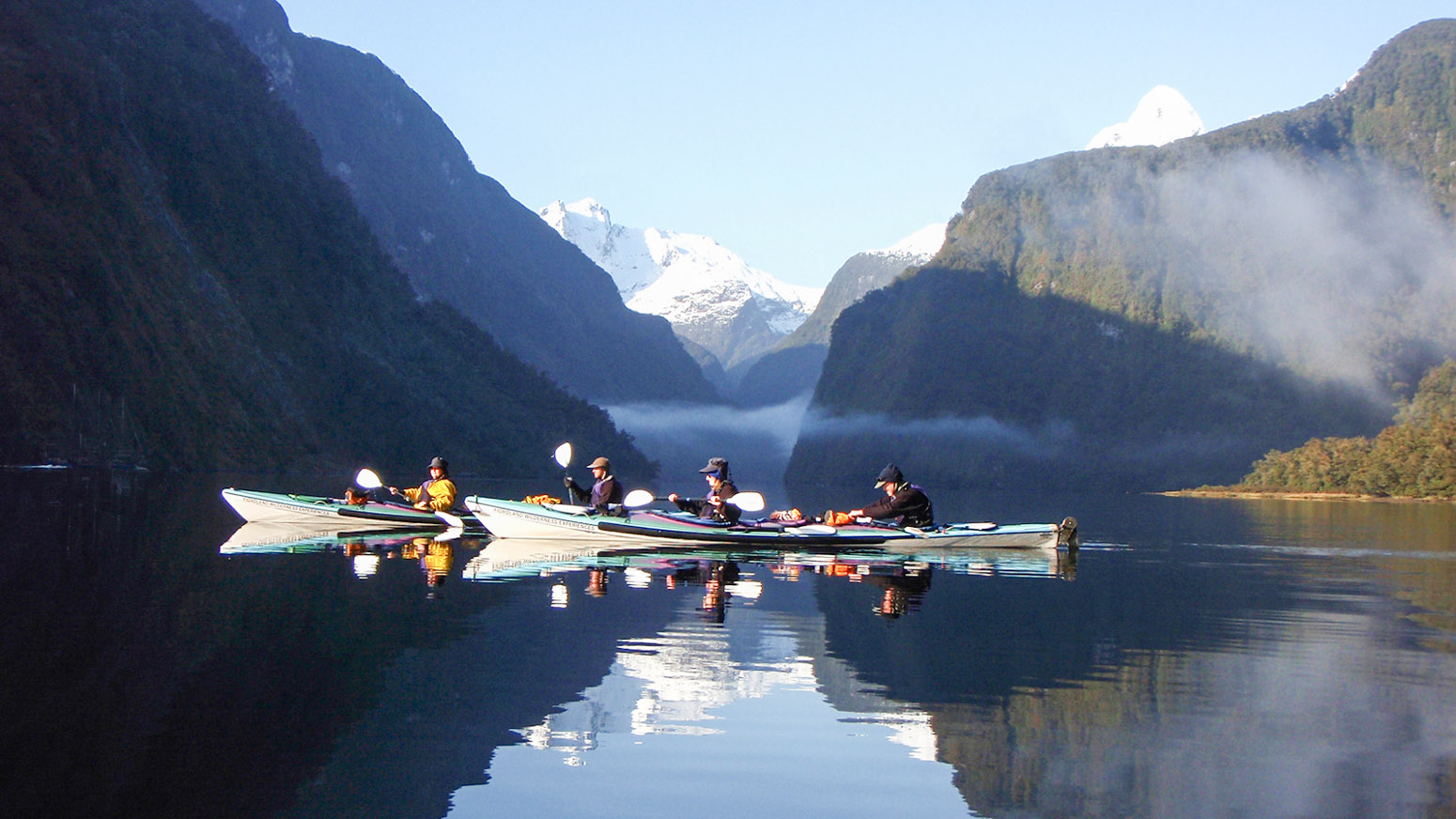 Sea kayakers reflected in the waters of Doubtful Sound