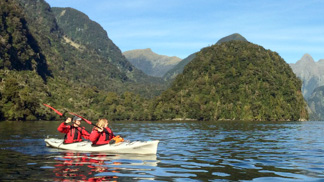 two girls kayaking on doubtful sound