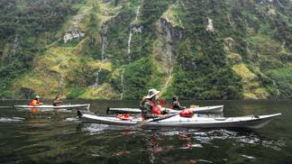 Guided sea kayakers kayaking past waterfalls in doubtful sound