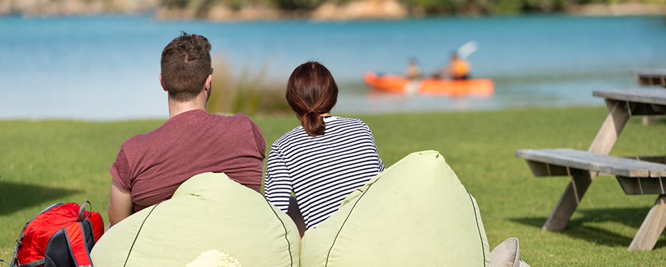 Couple relaxing at Otehei Bay, Urupukapuka Island, Bay of Islands