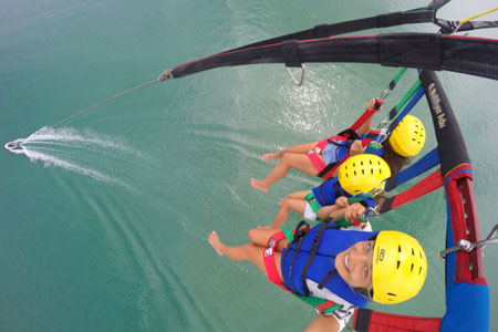 Three people high up on parasail trip, Bay of Islands