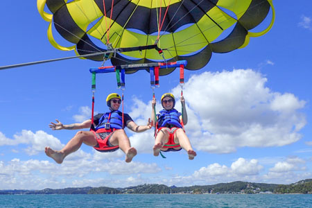Couple in tandem parasail water touchdown Bay of Islands