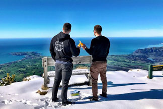 Two young men looking over Kaikoura Coastline from Mt Fyffe - Snow landing with Kaikoura Helicopters