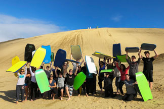 Group of backpackers sand boarding at Te Paki sand dunes, Cape Reinga