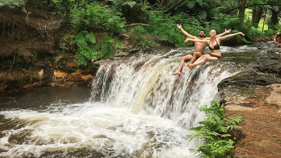 Young couple sitting on top of waterfall, Coromandel